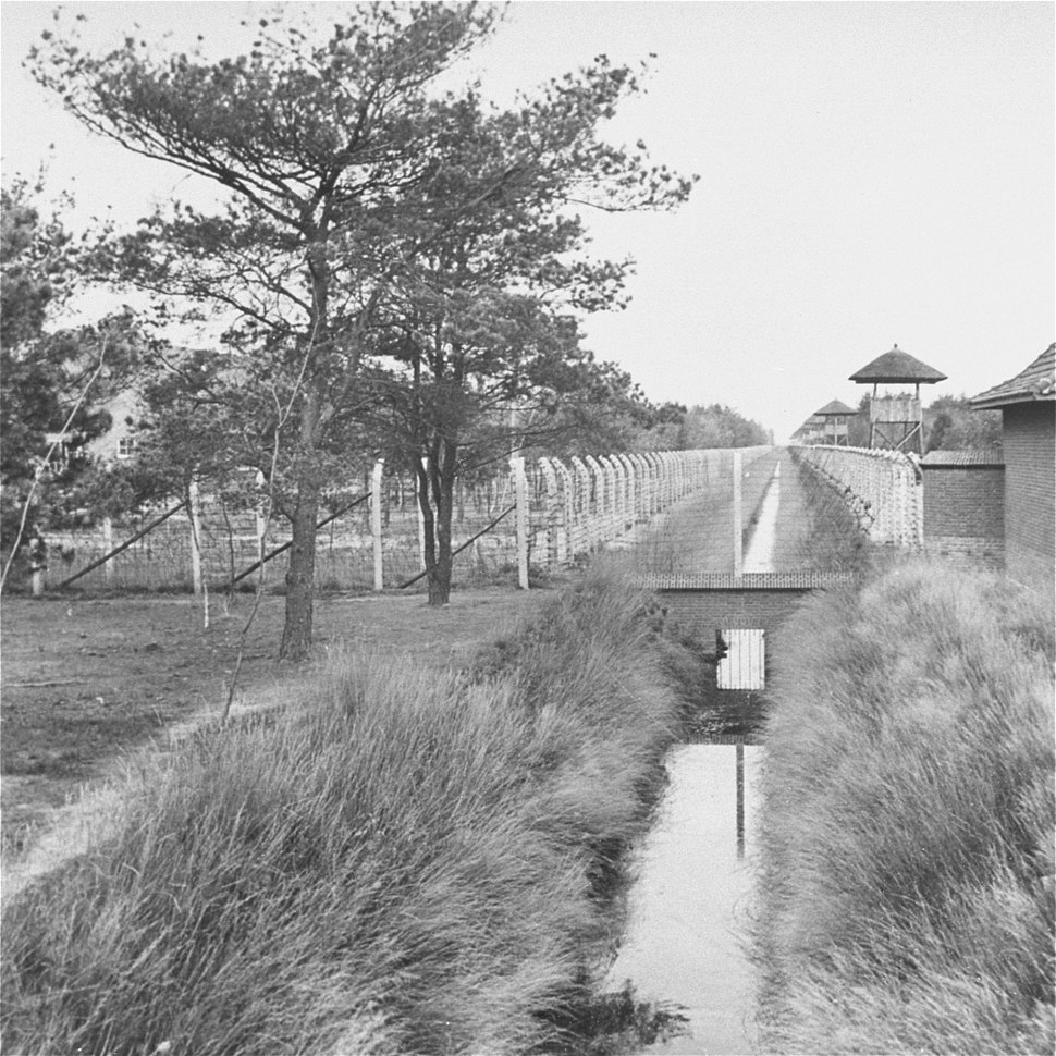 Black and white shot of a water-filled ditch, barbed-wire fences, and guard towers