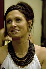 The 32-year-old Chambers wears a white dress with bare shoulders. She has numerous brown necklaces and a silver one. She has a chin stud below her lower lip and is looking to her right with a smile as she speaks.