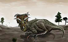 A big horned dinosaur in resting posture watches a small, feathered dinosaur