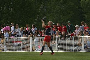 A light-skinned woman, wearing a red and blue shirt and red shorts, has her arms in the air to catch a ball in a grassy field as spectators look on.