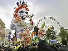 Vue d'un char de carnaval avec des masques au premier plan et une grande roue en fond.