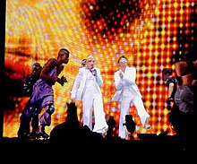 A female blond performer onstage wearing a white tuxedo and singing to a microphone in her left hand. A similarly dressed woman claps on her left. They are encircled by a group of guys in roller skates. The backdrop display disco lights in red and yellow.
