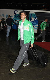 A white male leaving the bus wearing a Bulgaria national team tracksuit and pulling a suitcase behind him.