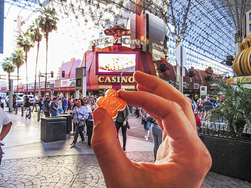 a hand holding up a weed edible candy with a clock and casino sign in the background