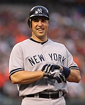 Mark Teixeira, wearing a dark blue baseball batting helmet and grey baseball uniform with the words NEW YORK across, takes off his batting gloves