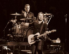 Middle-aged man with glasses wearing a dark shirt sits behind a drum kit on a riser with his right hand and stick about to hit a snare drum; he his looking directly at another middle-aged man in front of and slightly to the left of him, dressed in dark clothes with an electric guitar strapped to him, left hand on the frets, right hand flying away after playing a chord, eyes shut in an expression of conveying musical intensity of some kind