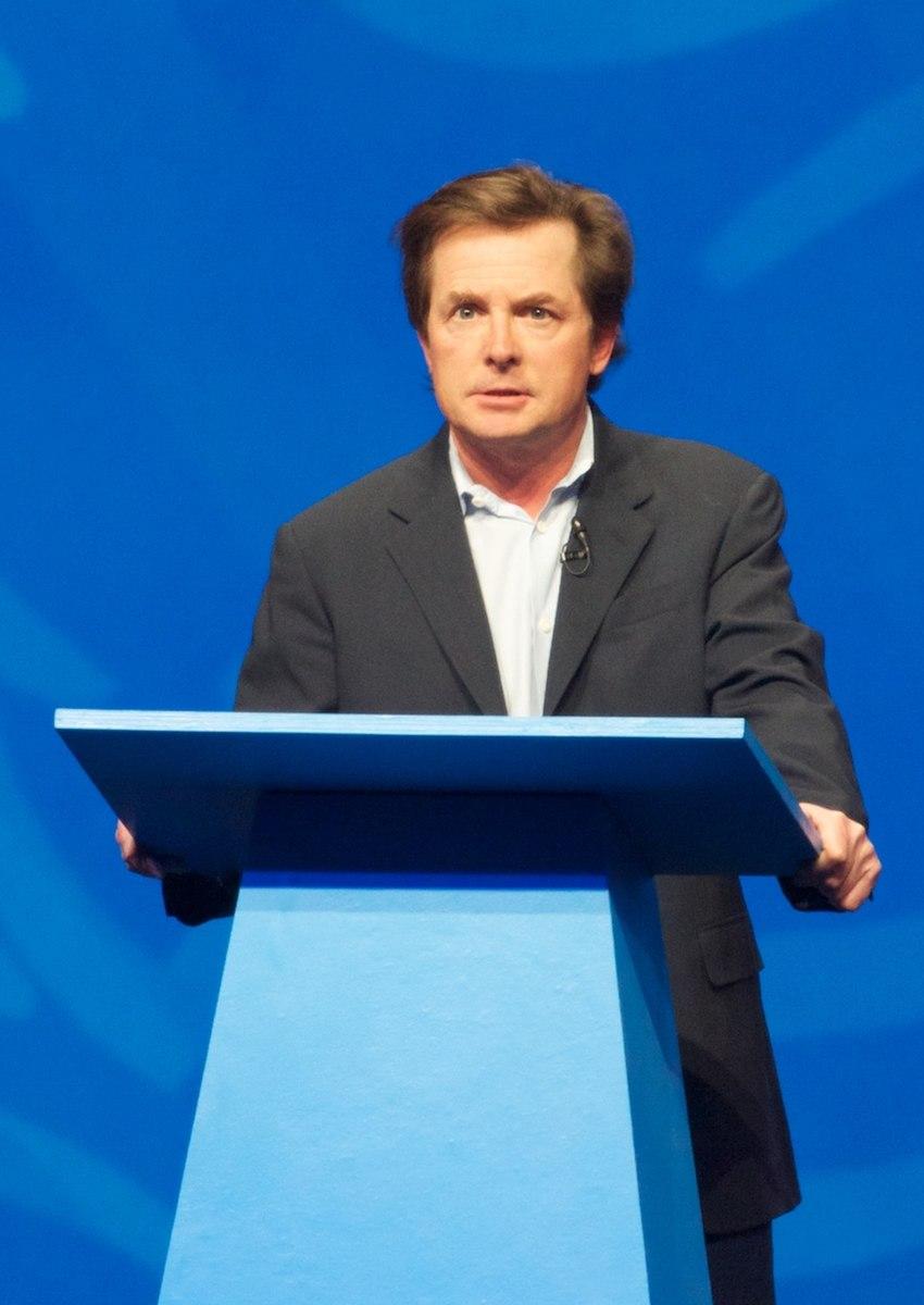 Foto de Michael J. Fox en un atril azul con fondo azul.