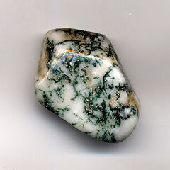 A smooth pebble of white agate with black and green dendrite formations.