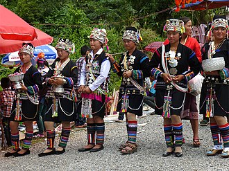 Akha people - That Xieng Tung Festival, Muang Sing, Laos. Akha young girls in the welcoming committee. On their arrival, visitors will have a color ribbon pinned to their blouse in exchange for a donation.