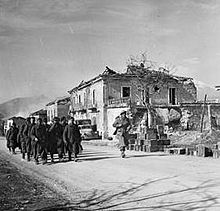 Soldiers march along a road past a stone building that has been damaged