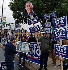 "Supporters of Yang's campaign raising signs that say ""Andrew Yang for President""."