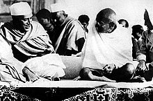 Two smiling men in robes sitting on the ground, with bodies facing the viewer and with heads turned toward each other. The younger wears a white Nehru cap; the elder is bald and wears glasses. A half dozen other people are in the background.