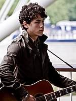A three-quarter portrait of a male teen looking forward. He has dark, curly hair, wears a black leather jacket, and strums a guitar hung over his shoulder.
