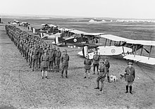 Black and white photograph of a large group of men dressed in military uniform standing in close formation next to a row of biplane aircraft