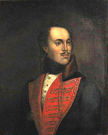 Picture of a painting of a man with a mustache wearing a red V collar; the man is slightly bald, and looking to his left.