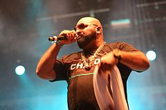 A bearded man wearing sunglasses, a chain, and a T-shirt reading 'CHABOS', rapping on-stage.