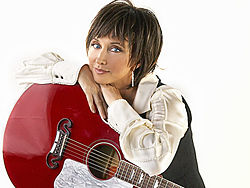 A woman with short brown hair, wearing a white shirt and leaning on a red guitar