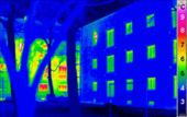 Thermogram of a passive house in the foreground and a traditional building in the background. Note the color to temperature key on the right.