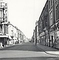 Photograph of Lynn Street taken by John Boagey, 1963. The photograph shows various shops on Lynn Street between Musgrave Street and Freeman Street including the large sign for the Empire theatre and (6328079765).jpg