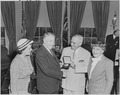 Photograph of President Truman in the Oval Office, shaking hands with Vice President Alben Barkley as he presents him... - NARA - 200220.tif