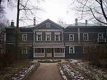 Una casa azul de dos pisos con adornos blancos y muchas ventanas, rodeada de abedules.