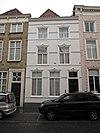 foto van Huis met gepleisterde en van stuckuiven boven de vensters voorziene lijstgevel, plat dak