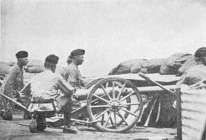 "Three artillery men crouch behind a small 2.5 inch ""Screw Gun"" employed in the defence of Kimberley"