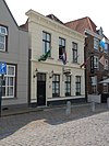 foto van Huis met witgepleisterde lijstgevel, vensters met afgeronde bovenhoeken en stucomlijsting