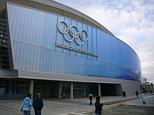 "Front of a building bearing the words ""Richmond Olympic Oval"" and a picture of five interlocking rings."
