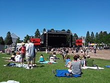 A bright blue sky over a lawn filled with people sitting on blankets or milling around, most facing a large stage with television screens on either side