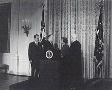 A formal-looking room with flags and drapery; in it, a middle-aged man, another middle-aged man with his right hand raised, a middle-aged woman, and an older man, are all beside a podium