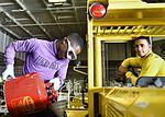 Sailors operate tractor in hangar bay 161015-N-UM507-004.jpg