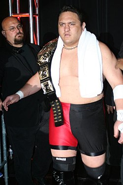 An adult male wearing red and black tights with black wrestling boots holding a black championship belt.
