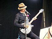 Colour photograph of Babyshambles lead singer Pete Doherty performing live in 2008. He is playing a guitar.