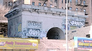 Seaman-Drake Arch - From the street. only the upper part of the arch can be seen over the commercial buildings that obscure it from full view (2015)