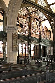 The interior of a church with an arch containing an elaborately carved screen in front of which are carved pews