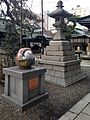 Stone lantern and sculpture of Kaga-Hachiman Roly-poly doll in Yasue Hachiman Shrine.jpg