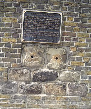 Surrey Iron Railway - Plaque and some of the original stone sleepers of the Surrey Iron Railway that were set in the wall of Young's Brewery in Wandsworth until the wall's demolition in December 2014
