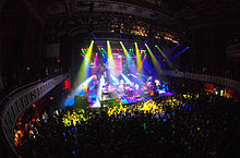 Multiple colored lights shine down on a stage while an audience watches.