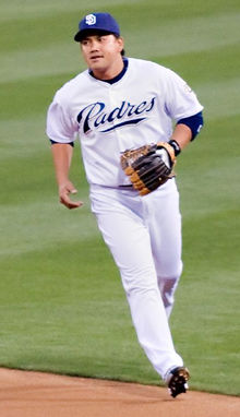 "A man wearing a white baseball uniform with ""Padres"" in navy blue script across the chest and a blue baseball cap atop his head"