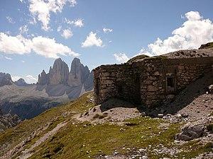 Le Tre Cime di Lavaredo viste dal Teston di Monte Rudo. In primo piano un rimasuglio di baraccamento della Prima Guerra Mondiale.