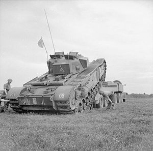 144th Regiment Royal Armoured Corps - Churchill tank of 144th Regiment Royal Armoured Corps being hauled onto a tank transporter at Burleigh in Hampshire, August 1942.