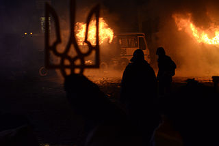 The state coat of arms of Ukraine, Tryzub, against background Dynamivska str barricades on fire. Euromaidan Protests. Events of Jan 19, 2014.jpg