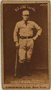 A baseball player is standing, holding a baseball bat down his right side.
