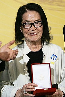 Photograph of Tomie Ohtake holding in her hands the Brazilian Order of Cultural Merit.