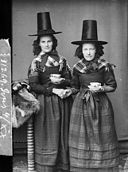 Two women in national dress drinking tea (Jones) NLW3362597.jpg