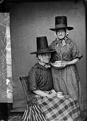 Two women in national dress drinking tea (Mellor)
