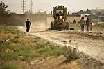 U.S. Air Force Staff Sgt. Jacob Snellings, assigned to the 577th Expeditionary Prime Base Engineer Emergency Force Squadron, drives a road grader toward the town of Payan Janqadam near Bagram Airfield 130613-F-YL744-171.jpg