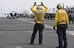 U.S. Navy Aviation Boatswain's Mate (Handling) 1st Class Andrew Jilcott, left, directs an F-A-18F Super Hornet aircraft assigned to Strike Fighter Squadron (VFA) 154 as Aviation Boatswain's Mate (Handling) 130619-N-GA424-229.jpg