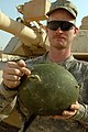 US Army 51272 BAGHDAD - Pfc. James Freed, of Odon, Ind., points to the exit hole a bullet made through his helmet when a sniper attacked him while on patrol in the Sadr City area in June. Freed, a tanker assigned t.jpg